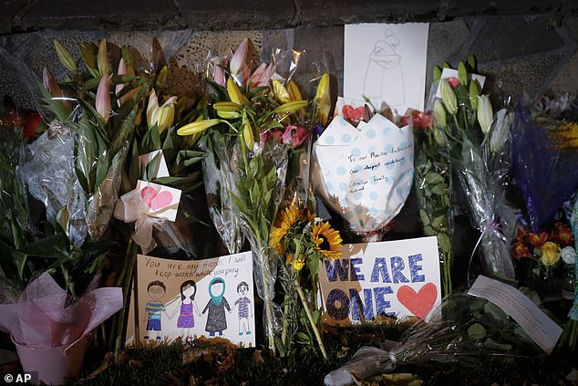 Mourners place flowers as they pay their respects at a makeshift memorial near the Masjid Al Noor mosque in Christchurch, New Zealand, Saturday. New Zealand's stricken residents reached out to Muslims in a fierce determination to show kindness to a community in pain as a 28-year-old white supremacist stood silently before a judge, accused in mass shootings