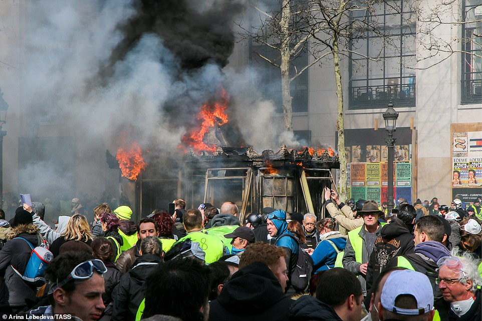 A small structure is on fire in the centre of a busy pavement as yellow vest protests continue in Paris