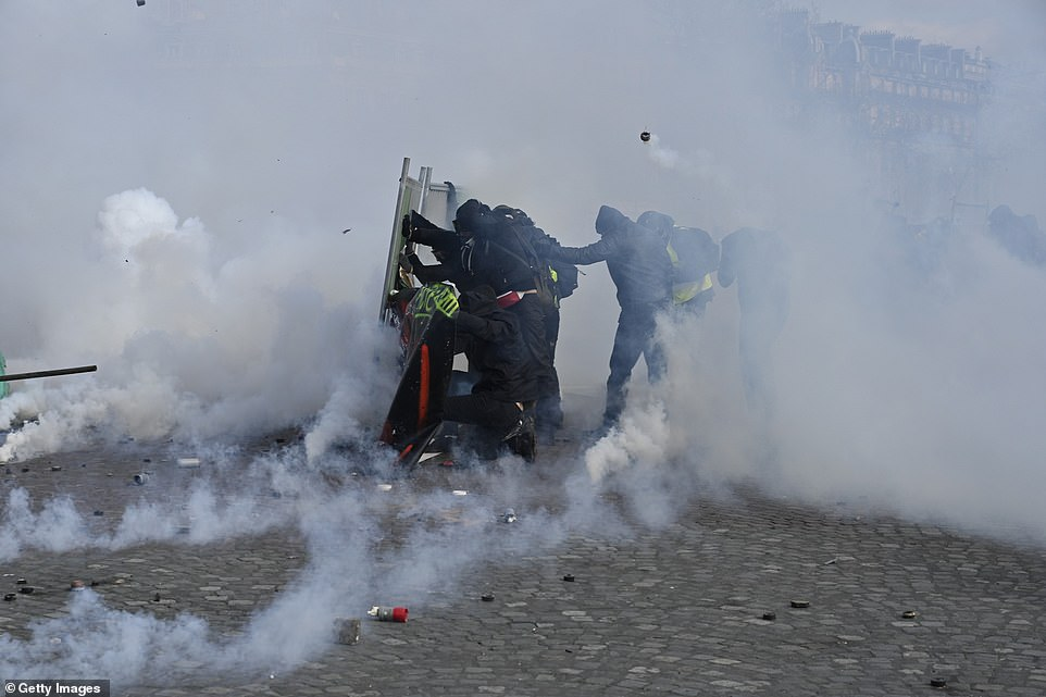 Protesters are pictured setting up a barricade against the teargas during the 18th yellow vest demonstration,so-called 'Act XVIII'