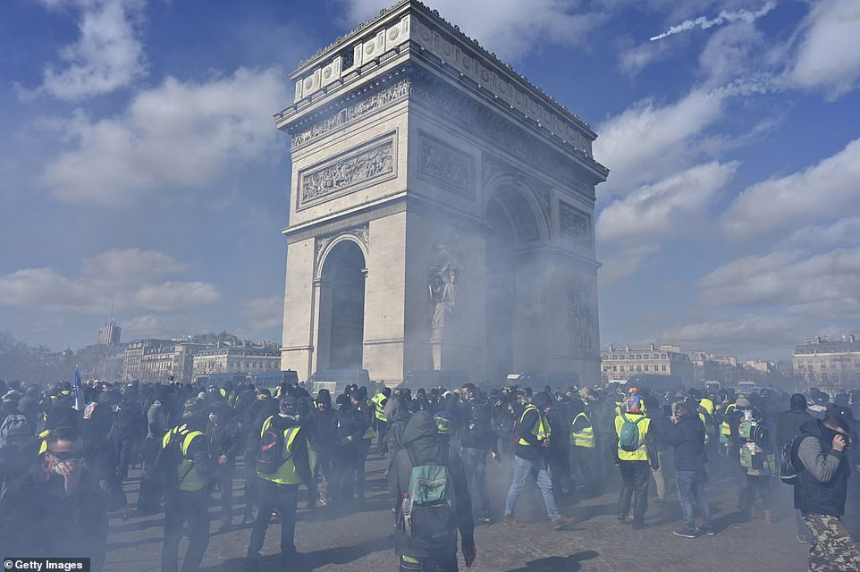 Protesters cover their faces and disperse momentarily after tear gas is fired into the crowd near Champs Elysees