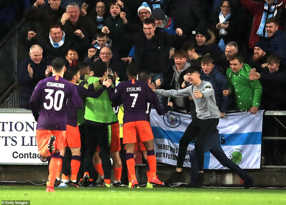 The Manchester City players celebrate with their supporters following Augero's late goal