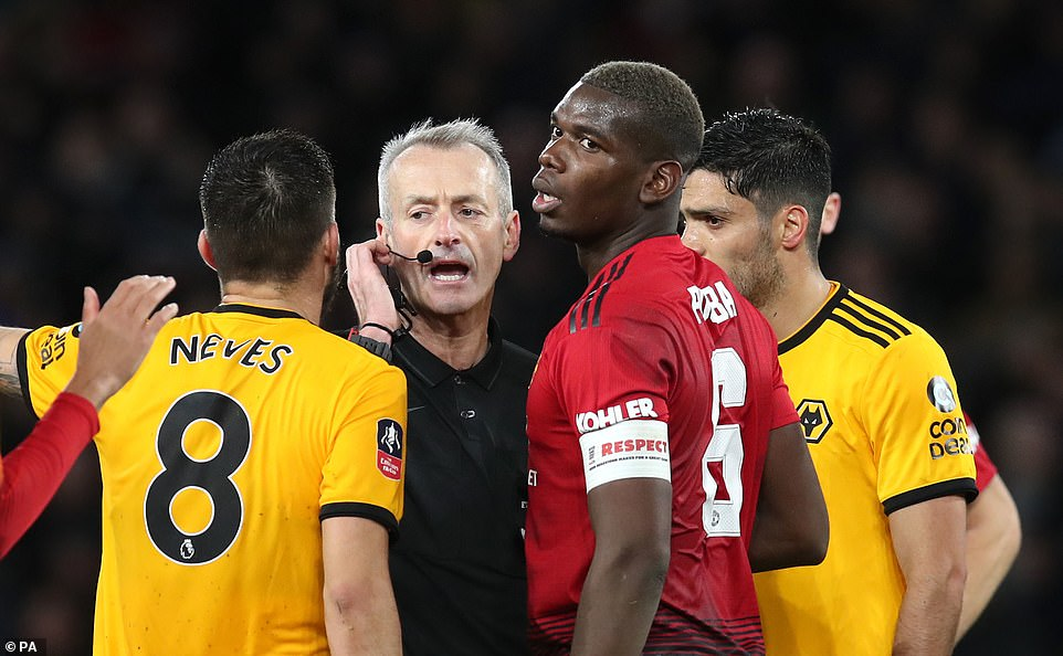 Wolves' Ruben Neves (left) and Manchester United's Paul Pogba speak to match referee Atkinson during the first half