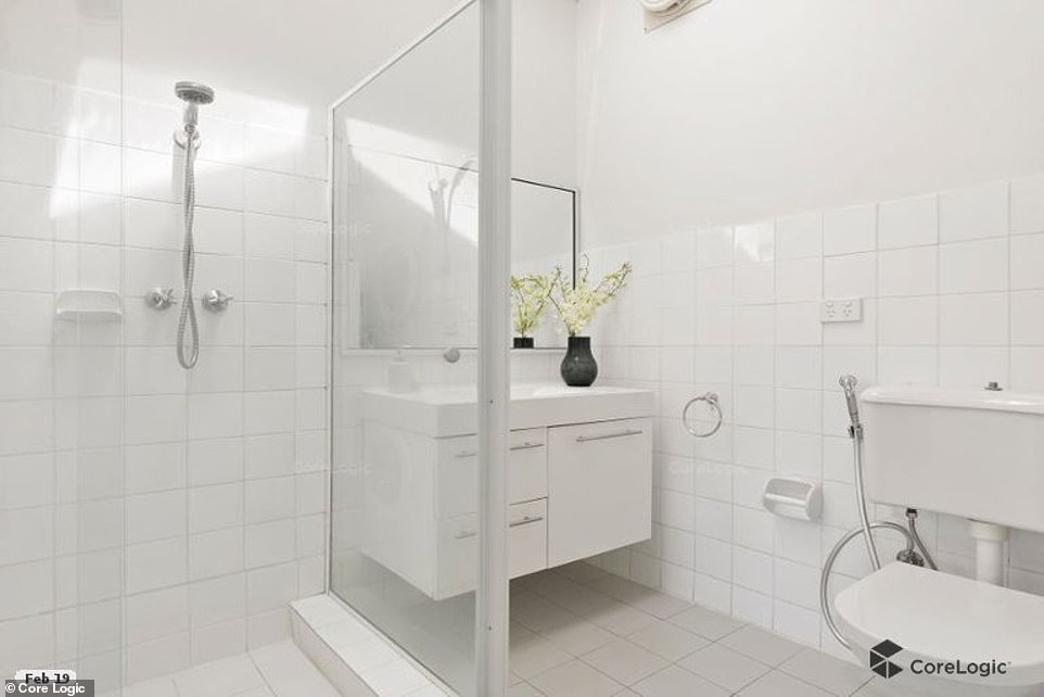 Modern: The bathroom is simple yet chic with white tiles and cabinetry