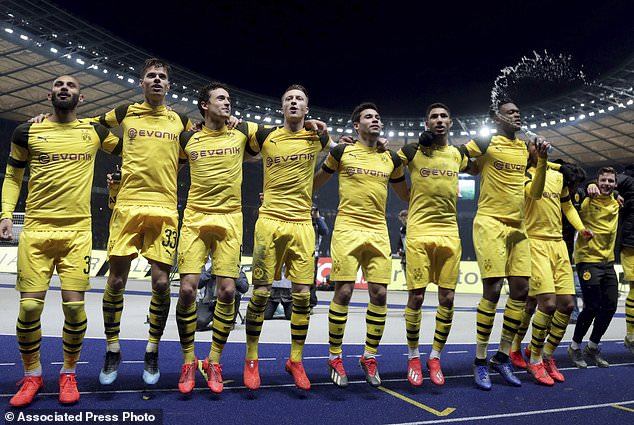 Dortmund's players celebrate in front of their supporters after the German Bundesliga soccer match between Hertha BSC Berlin and Borussia Dortmund in Berlin, Germany, Saturday, March 16, 2019. Dortmund defeated Berlin by 3-2. (AP Photo/Michael Sohn)
