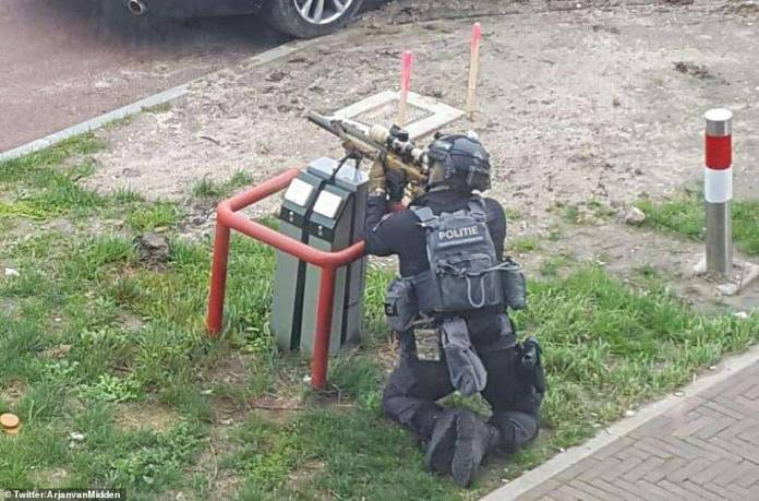 A photo shared on social media shows an armed policeman surrounding a building in Utrecht during the manhunt