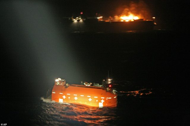 The lifeboat carrying the members of the crew is seen in the foreground while the burning cargo ship is seen in the background