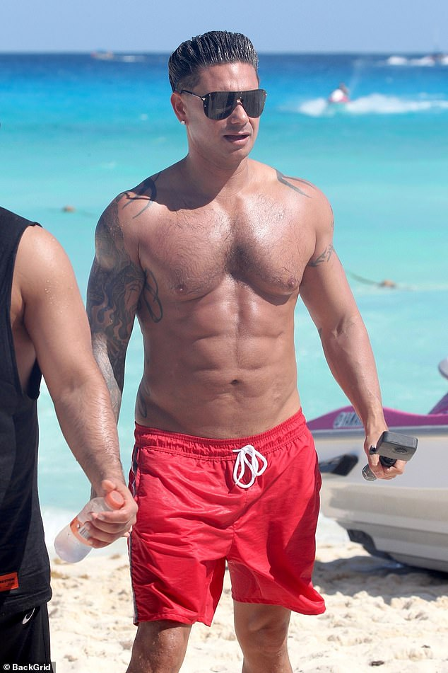 Sculpted: Wearing only a pair of red shorts, the DJ showed his washboard abs