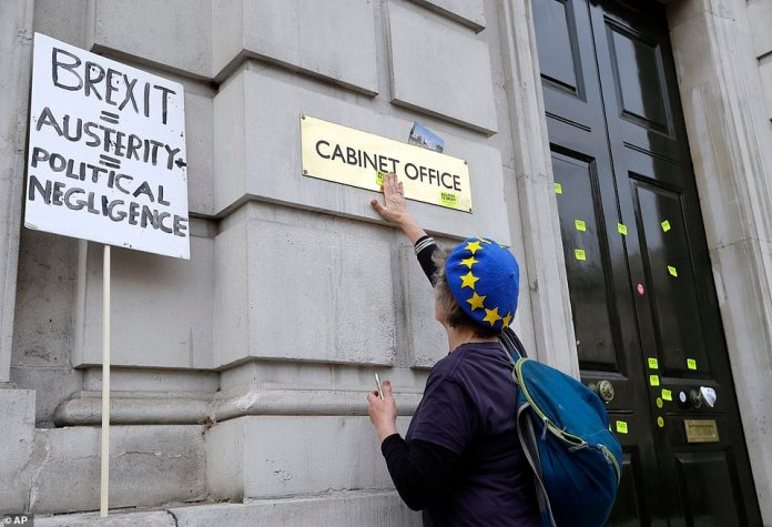 A demonstrator paste an anti-Brexit sticker by the entrance of the UK government's Cabinet Office during Saturday's protest