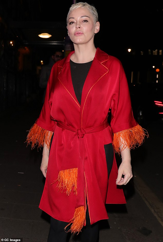 Eye catching: Rose McGowan turned heads in on Friday night, donning a beautiful red kimono wrap style top with orange feathers for a night out at Annabel's in London