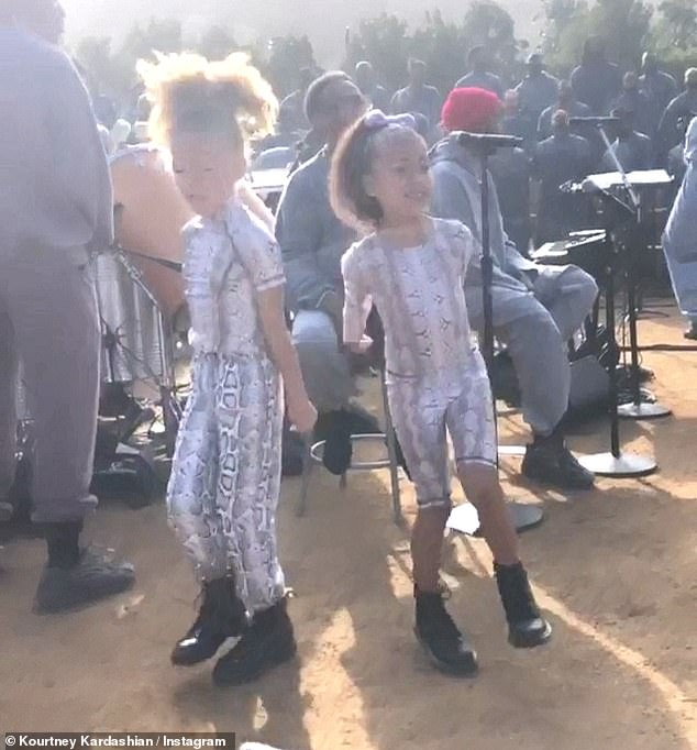 Matching: Kim co-ordinated her eldest daughter North, five, who managed to watch her own snakes dancing with her friend at the service, run by Kanye's father.