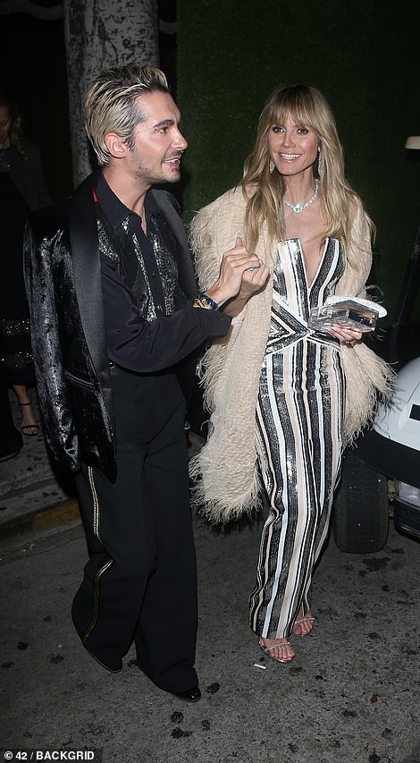 Party people: Heidi looked at the star-studded bash with male pal, giggling away