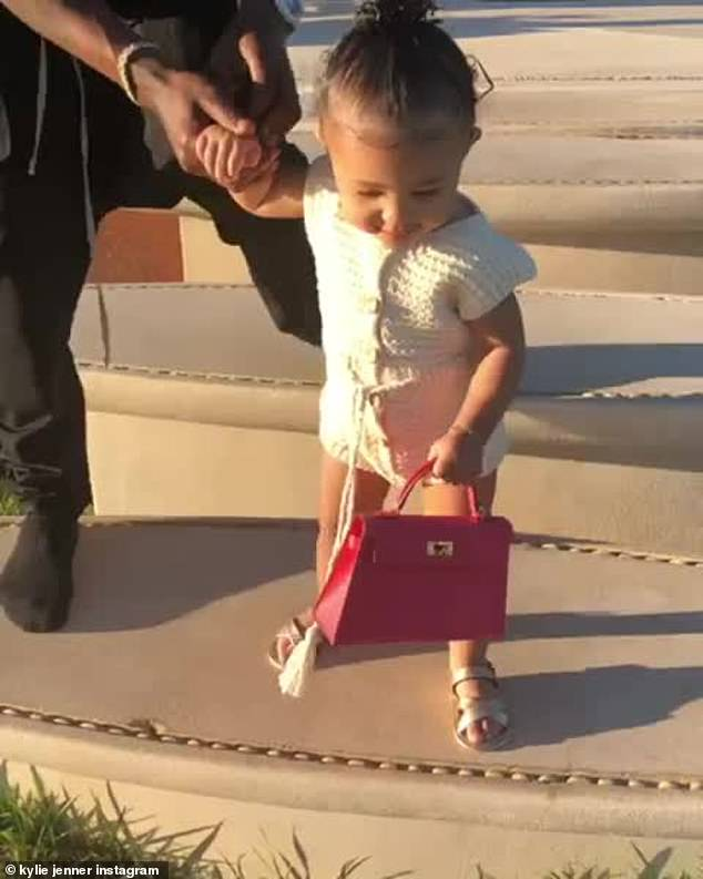 Rose: Last year, little Stormi also wore a pink Hermes Kelly mini bag in two different positions;  with her daddy Travis