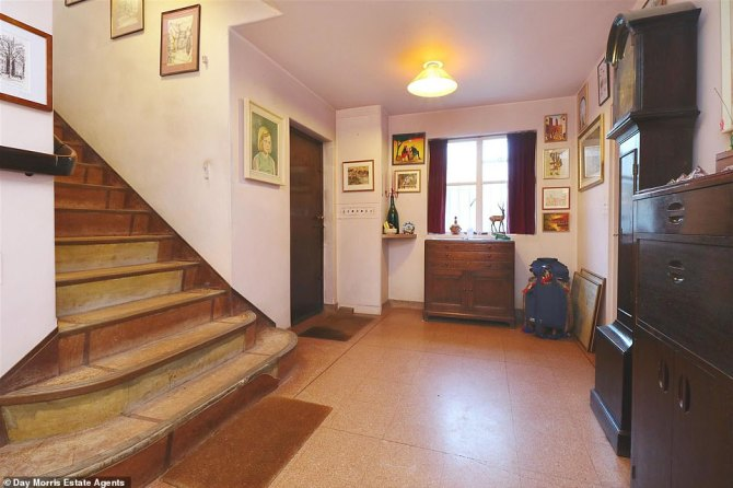 A large entrance hallway leads to the upstairs areas of the house via a pealing lino staircase. An imposing old grandfather clock stands opposite the staircase and multiple works of art decorate the walls