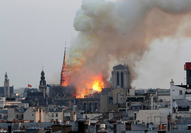 The spire seen leaning slightly over as it began to give way because of the fire ripping through its foundations and the rest of the roof