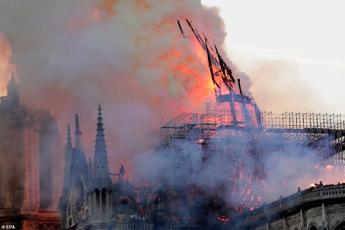 The spire collapses while flames are burning through the roof at teh Notre Dame Cathedral in Paris today. The blaze started in the late afternoon at one of the most visited monuments in the French capital