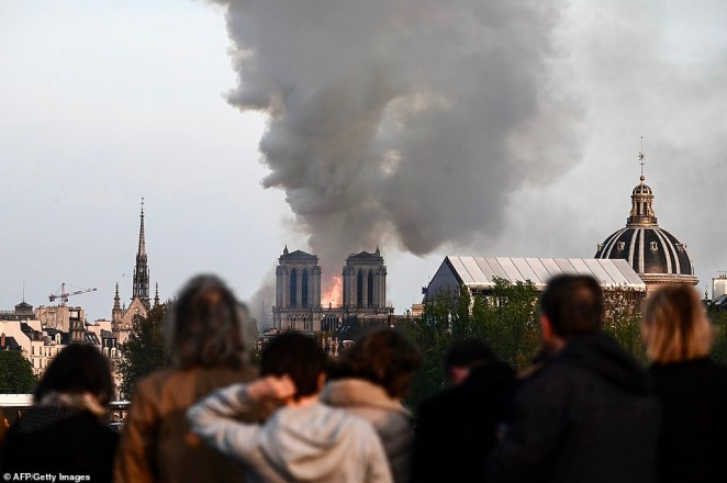 Parisians and toursits look on in utter shock as the flames engulf the historic cathedral, which is visited by millions every year