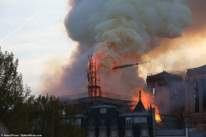 A shard of the cathedral's spire plummets through the air as it collapsed earlier after the fire burned through its foundations