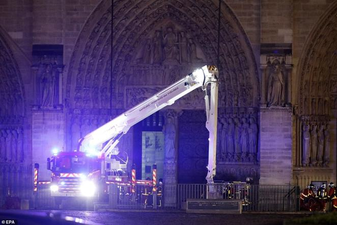 French fire crew gather on the parvis in front door of the Notre Dame Cathedral on Monday evening as flames are burning its roof in Paris