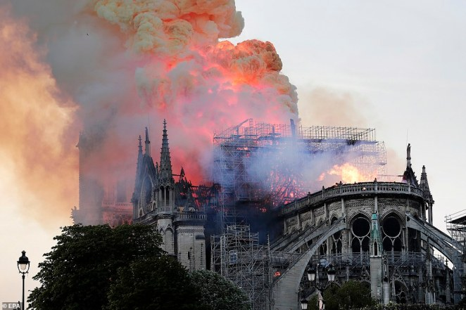The flames and smoke engulf the historic gothic building on Monday afternoon. Parisians prayed and cried as they watched it burn