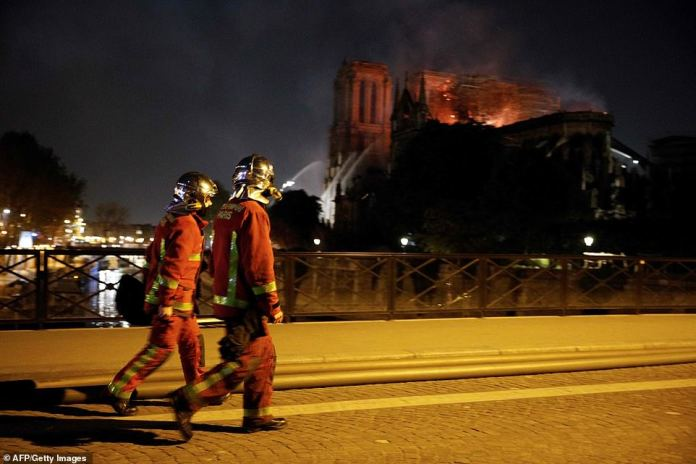 Firefighters look on at the fire fire at the landmark Notre-Dame Cathedral in central Paris as they cross a bridge over the river Seine