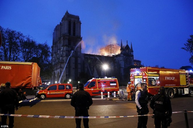 A cordon is in place as fire crews spray water on the Gothic cathedral to try and stem the flames this evening