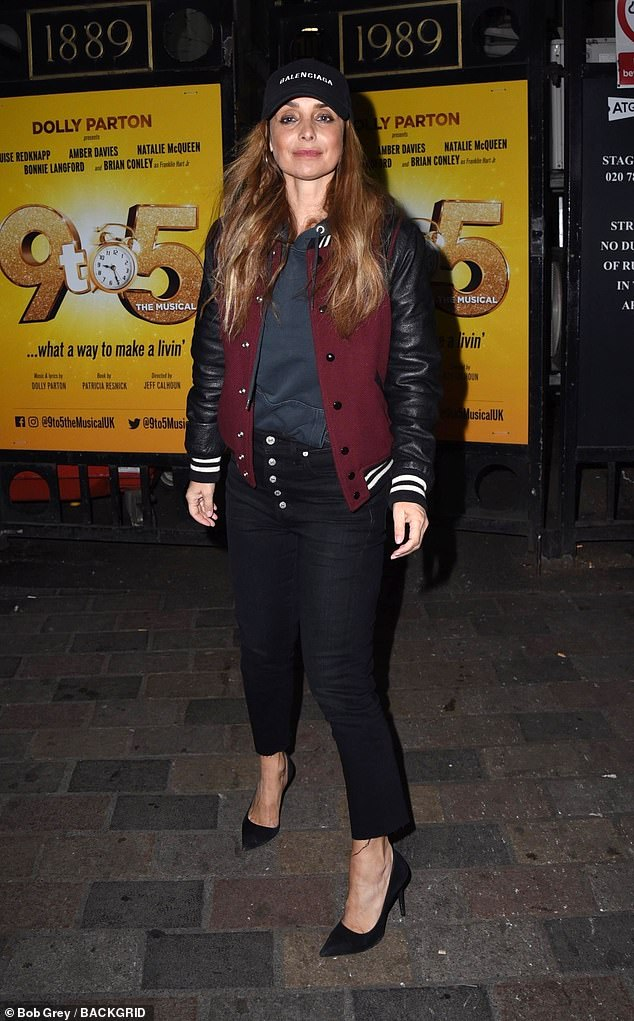 Trendy: The 44-year-old cut at trendy figures outside the Savoy Theater wearing a black button up jeans, a gray hoodie and a letterman jacket with leather sleeves