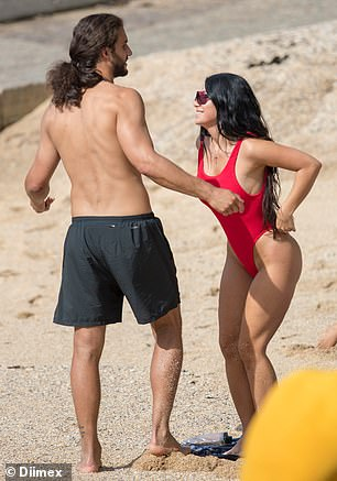 Need a hand? The brunette required Michael's assistance as she made an awkward adjustment to her swimsuit