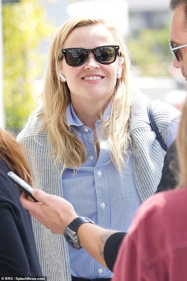 Connected: Reese wore her blonde hair tucked behind her ears, revealing AirPods, and sported black-framed sunglasses