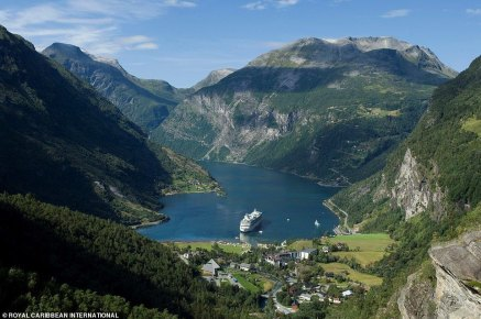 Royal Caribbean's Vision of the Seas cruises down a fjord towards the village of Geiranger in western Norway. Although the boat has ten decks and can hold 2,416 guests, it's dwarfed by the towering mountains surrounding it.Even though Geiranger is located more than 100 kilometres (62 miles) inland from the coast, it is the second largest cruise port in Norway