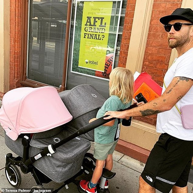 The model posted several photos of the trip to Instagram with the caption, 'First city stroll! Off to get Poet her birth certificate. Pushing all three kids on our pram.' Pictured: Mark Webber (right) with son Bodhi