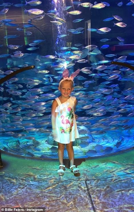 Holiday of a lifetime: Nellie looked delighted as she posed for a snap in front of the aquarium in white bunny ears