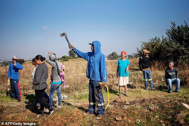 A person in the 'colored' community of Eldorado Park raises a hatchet during a land grabbing action on the outskirts of Johannesburg. The community continues to feel a sense of injustice in a new South Africa