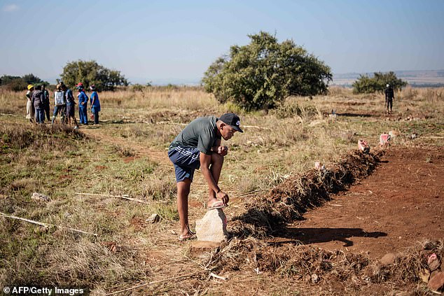 A man belonging to the 'colored' community of Eldorado Park prepares a clearing in a plot of land during a land grabbing action on the outskirts of Johannesburg