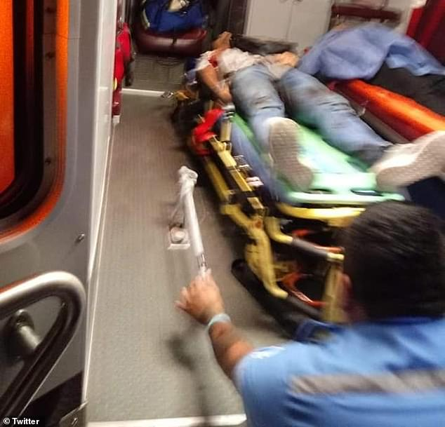 A paramedic in Playa del Carmen places a shooting victim inside an ambulance after two men allegedly shot up a restaurant in what government officials said was related to a criminal organization seeking extortion payment
