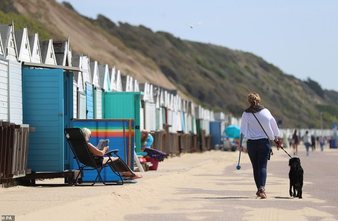 A woman is pictured walking her dog on the beach at Boscombe in Dorset while people sunbathe outside their beach huts