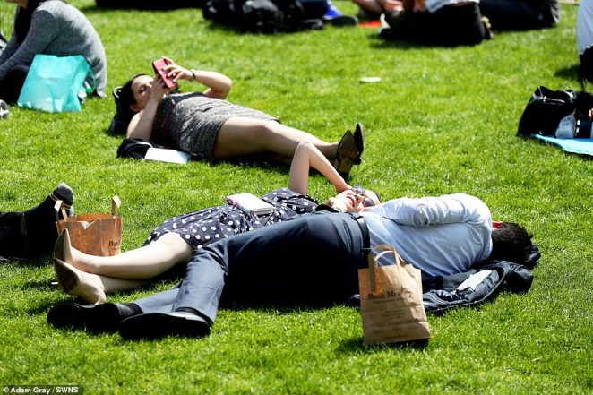 Here comes the sun! Workers are pictured relaxing in the sunshine during their lunch breaks in central London today
