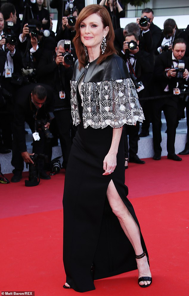 Leggy display: The 58-year-old turned heads in a classic black floor-length gown with a thigh-high slit that showed off her trim pins and chic black heels