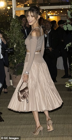 Details:She teamed the item of clothing with a ruffled midi skirt, which completed the stylish three-piece co-ord