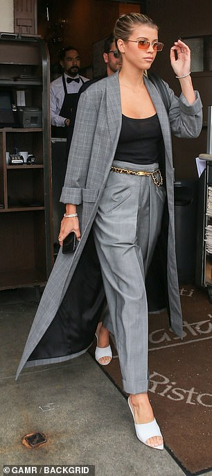 Richie put on a stylish show in a gray check coat and matching trousers fastened at the waist with a gold chain