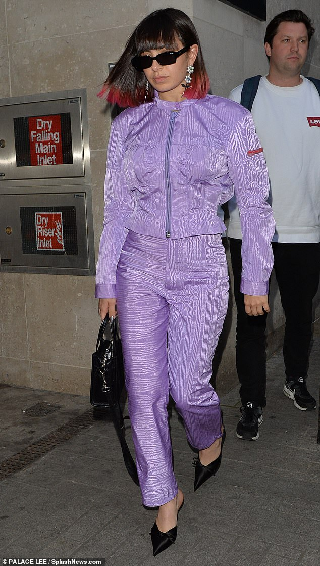 Stepping out: While she is known for racy outfits, the 26-year-old was seen leaving at the BBC Radio 1 studios in a modest, yet eye-catching lavender tracksuit combo