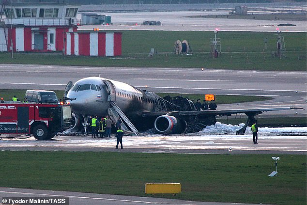 Salvage: Rescue workers at the scene after the passengers evacuated the jet after the emergency landing in Moscow