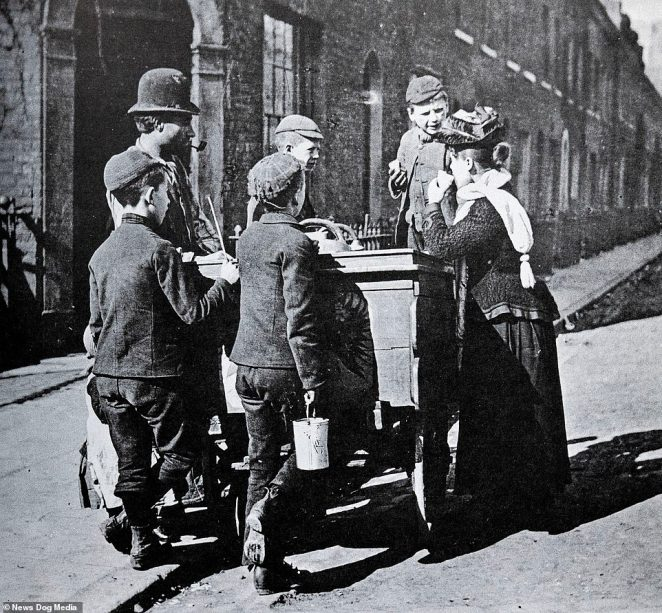 A group of children speak to a man and woman at an ice cream vendor's cart in Lambeth in 1892, in this photo by Mr Martin
