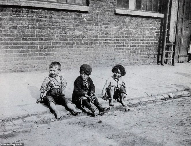 Three children look mischievous as they sit on the kerb in London in filthy clothes and their faces covered in dirt in 1892 - with only one of them wearing shoes. Victorian photographer Paul Martin described them as 'human squirrels' in a note