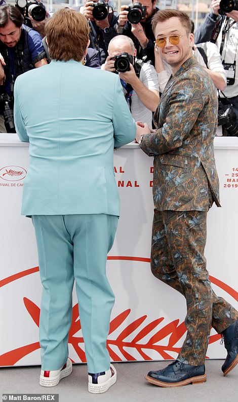 They got the memo: Elton and Taron larked around while dressed in flamboyant suits and glasses as they greeted fans