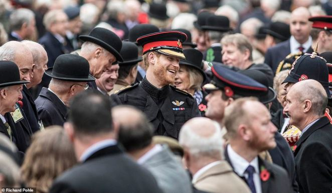 Prince Harry chats with veterans during the opening of the garden of remembrance at Westminster Abbey. It is among the images showcasing the work of the British press over the past year