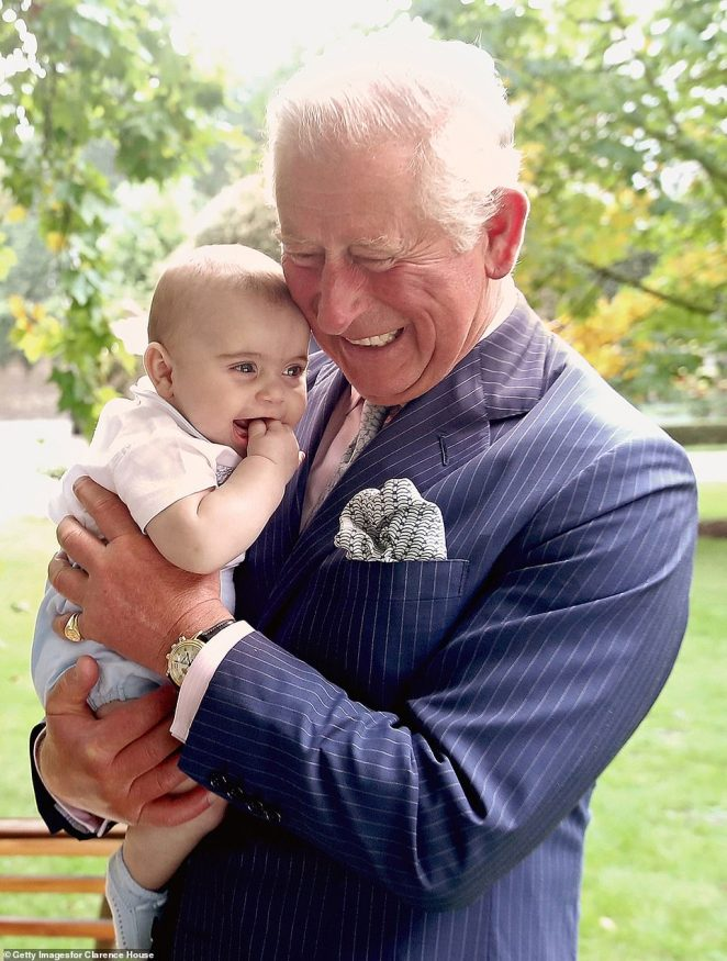 Prince Charles, Prince of Wales holds Prince Louis of Cambridge after a family portrait photo-shoot in the gardens of Clarence House in September last year