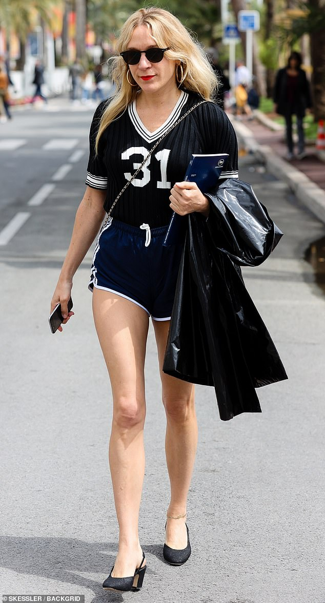 Pins for days: The actress put on a leggy display by pairing a pair of tiny sport shorts with a black T-shirt emblazoned with the number 31