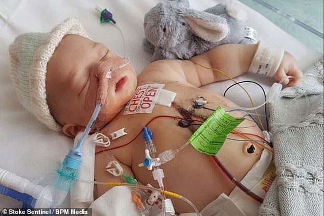 Riley, who is now 11 months, suffered another cardiac arrest three months later and was whisked to hospital in an ambulance (pictured in hospital)