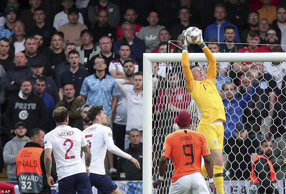 England goalkeeper Jordan Pickford (No 1) leaps to catch the ball after a cross is whipped into the area