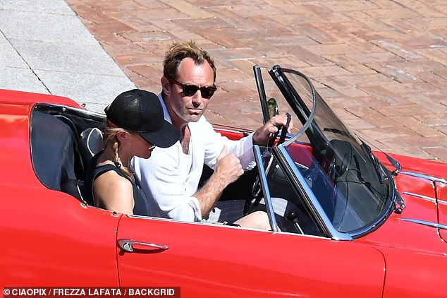 Taking in the sights: Jude proved to be every inch the hunk in a neutral white ensemble as he got behind the wheel to take Phillipa sight-seeing